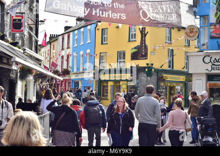 Streets within pedestrian zone in Galway center with tourists enjoying sunny day. - Stock Photo