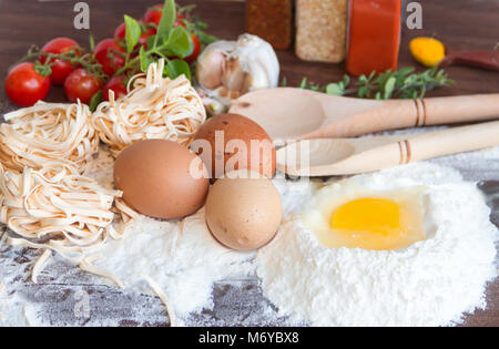 ingredients preparation spaghetti with eggs, tomatoes herbs and spices - Stock Photo