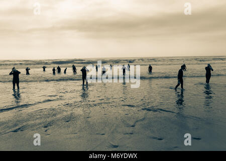 Triathlon beach athletes silhouetted swim preparation for race start in ocean water course at dawn sunrise vintage - Stock Photo