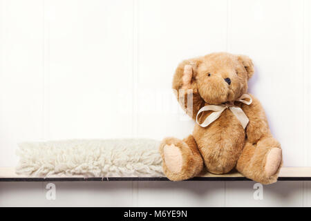 Teddy bear on shelf with sheepskin rug digital background. - Stock Photo
