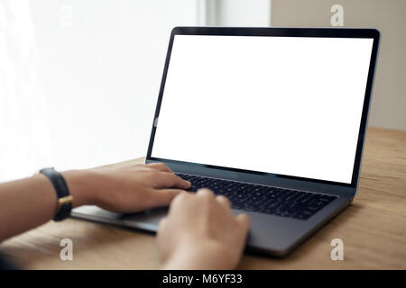 Mockup image of hands using and typing on laptop with blank white desktop screen on wooden table - Stock Photo