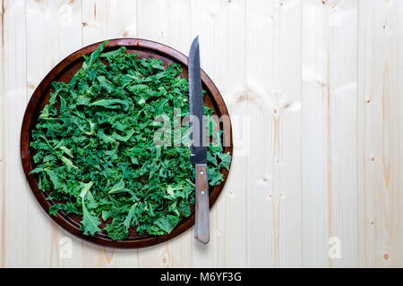 Fresh chopped prepared kale on old metal platter with knife - Stock Photo