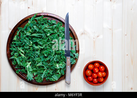 Fresh chopped prepared kale on old metal platter with knife with bowl of cherry tomatoes for salad or smoothie with - Stock Photo