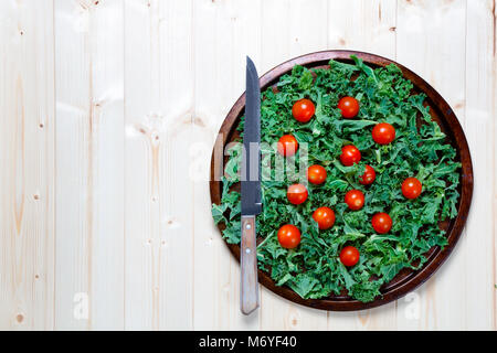 Fresh chopped prepared kale with cherry tomatoes on metal tray with knife with copy space - Stock Photo