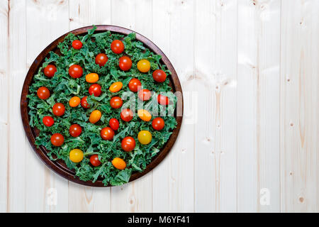 Fresh chopped prepared kale with yellow and red cherry tomatoes on metal tray with knife with copy space - Stock Photo