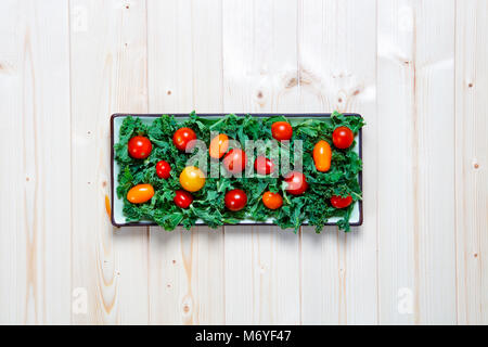 Fresh chopped prepared kale with yellow and red cherry tomatoes on plate with knife with copy space - Stock Photo