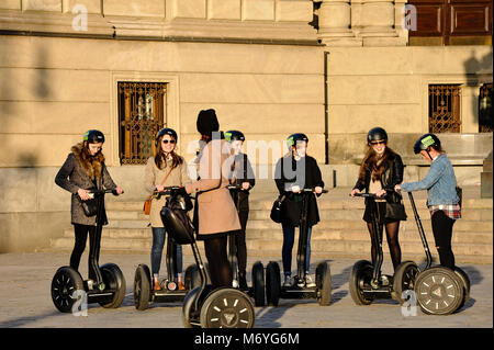 Prague, Czech Republic city centre. Happy group of tourists having guided sunset tour on Segway scooters - Stock Photo