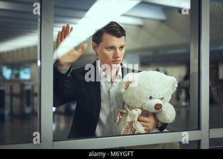 Sad man with a toy bear waiting for a meeting. He looks out the window - Stock Photo