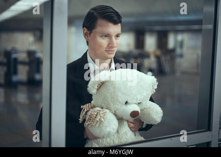 Young man looks out the window and smiles. He has a teddy bear in his hands - Stock Photo