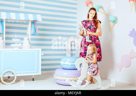 Little girl sits on a wooden horse, her mother standing next - Stock Photo
