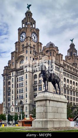The Liverpool Insurance building reaches into the cloudy skies over the city. Before it, stands an equestrian statue - Stock Photo