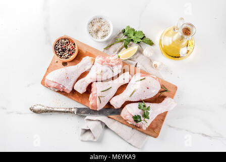 Raw meat, chicken legs, with olive oil, herbs and spices, on white marble background, copy space top view - Stock Photo