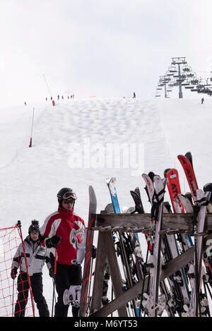Pairs of Skis in a Rack at the Bottom of a Ski Run with Chairlift and Mogul Slope at Les Gets near Morzine Haute - Stock Photo
