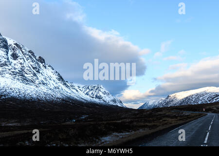 Deserted road into the Glencoe valley on a cold winter day in the scottish highlands. - Stock Photo