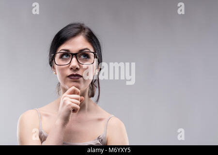 Attractive woman wearing glasses deep in thought looking up with a serious pensive expression and her hand to her - Stock Photo