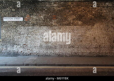 Weston Street Brickwall inside tunnel with pavement and yellow lines showing - Stock Photo