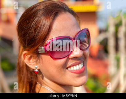 Close-up head and shoulders portrait of a beautiful Filipino woman with a great smile wearing sunglasses in the - Stock Photo