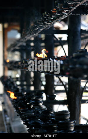 Oil lamps burning in candy Temple 2006 Sr Lanka - Stock Photo
