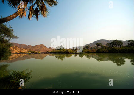 Placid waters of the Kunene river near Epupa Falls on the Angola border, Kunene region. On the other side of the - Stock Photo