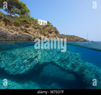 Rocky coast with a small house and a natural rock formation underwater in the Mediterranean sea, split view above - Stock Photo