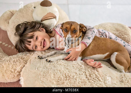 Six year old girl and her doggie laying on a giant bear - Stock Photo