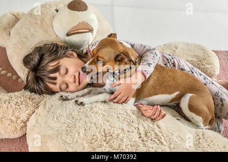 Six year old girl being kissed by her dog on a giant bear - Stock Photo