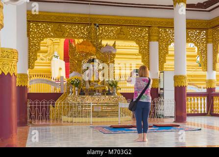 Tourist taking a photo of Buddha statue at Kuthodaw Pagoda, Mandalay, Myanmar (Burma), Asia in February - Stock Photo