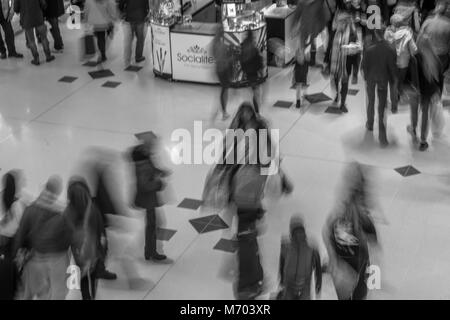 People walking through a shopping mall, taken with a slow exposure to blur the people and add the impression of - Stock Photo