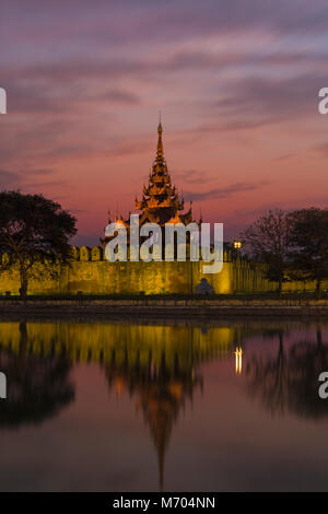 Moat bastion and city wall of Mandalay Royal Palace at sunset with reflection in water, Mandalay, Myanmar (Burma), - Stock Photo