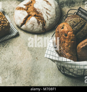 Various bread loaves on grey concrete background, square crop - Stock Photo