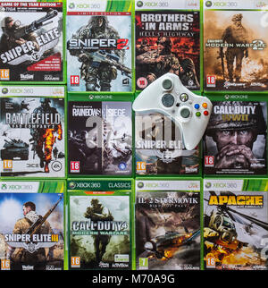 Controller and collection of violent first-person shooter video games for Xbox 360 and Xbox One - Stock Photo