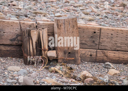 View showing part of a groyne on a beach with rocks and sand round about. - Stock Photo