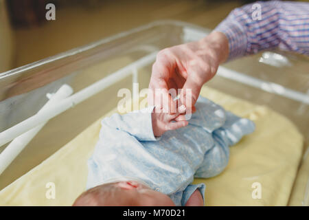 the father holds the handle of the baby in the hospital - Stock Photo