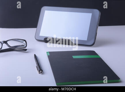 Modern white office desk table with laptop, smartphone and other supplies. Blank notebook page for input the text - Stock Photo