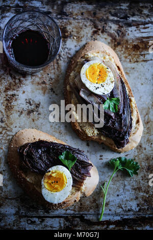 Braised red chicory crostini with hummus, boiled egg and spices - Stock Photo