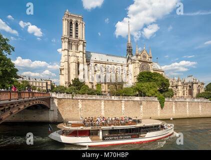 PARIS, FRANCE:  Bateaux Mouche on the River Seine passing Notre-Dame Cathedral on the Ile de la Cite - Stock Photo