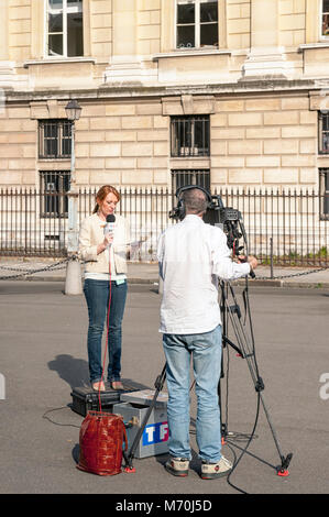 Outside Broadcast  TV Cameraman and Presenter at work filming in Paris, France - Stock Photo