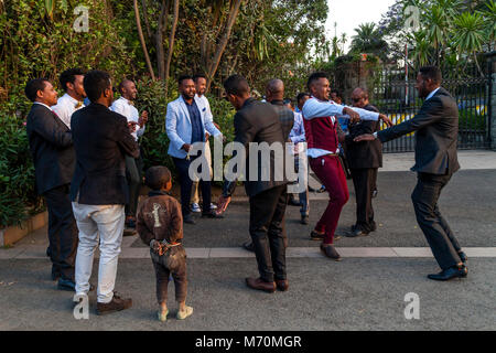 Male Members Of A Bridal Party Dancing In The Street Watched By A Bemused Street Boy, Addis Ababa, Ethiopia - Stock Photo