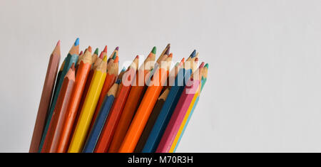 Colored pencils in a jar on a pale background - Stock Photo