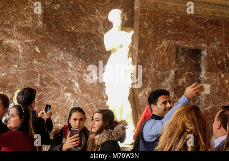 people taking photos in front of the Venus de Milo sculpture by Alexandros of Antioch, Louvre Museum, Paris, France - Stock Photo