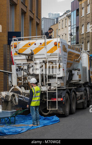 construction workers and builders on a site in central london pouring concrete from a ready mix lorry into wheelbarrows - Stock Photo