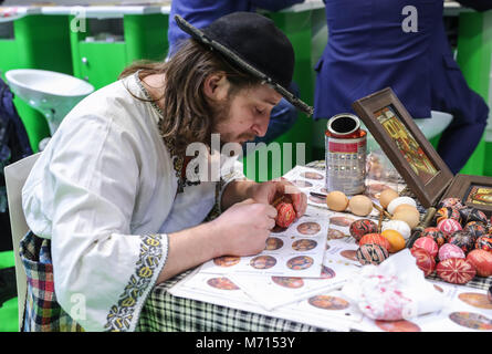 Berlin, Germany. 7th Mar, 2018. A staff member paints an egg at the Romania's booth during ITB Berlin in Berlin, - Stock Photo