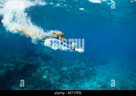 Happy family - active teenage girl jump and dive underwater in tropical coral reef pool. Travel lifestyle, water - Stock Photo