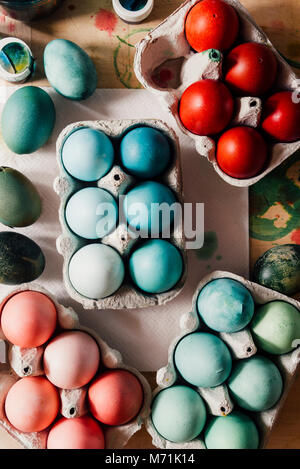 Dyeing eggs for Easter holidays, colored eggs with blue tint and different tonality ainside a package over a gray - Stock Photo