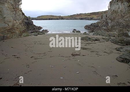 Footprints in the sand of a quiet sandy cove, on the coast of West Cork, Ireland. - Stock Photo