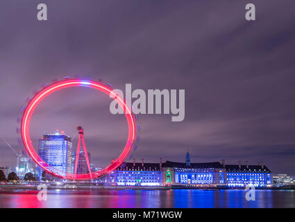 The London Eye and County Hall  illuminated  red and blue on a cloudy November evening. - Stock Photo