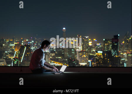 Asian businessman sitting and using the laptop over the cityscape background at night time, Business success and - Stock Photo