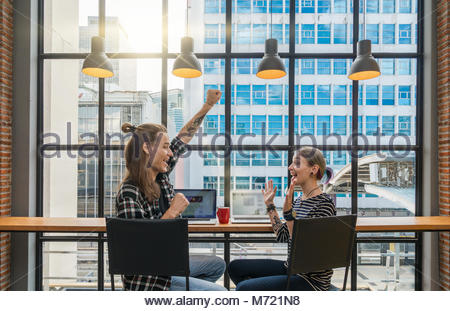 Backside of Hipster young couple freelancer using smart Laptop for working in the Loft cafe workplace. Creative - Stock Photo