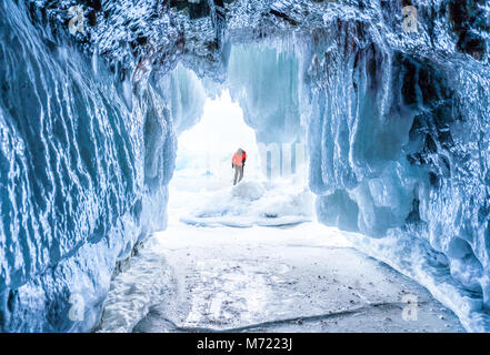 Winter Landscape, Frozen ice cave with young photographer standing alone. Traveling in winter - Stock Photo