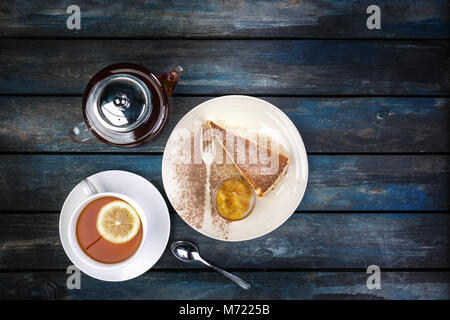 Slice of Cheesecake with jam and tea kettle with lemon on a colored wooden background. Top view - Stock Photo